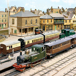 At Madderport Station loco Manx Kitten arrives with her train and Welsh Pony is about to depart. Behind them can be seen the handsome Georgian-style Harbour Office.