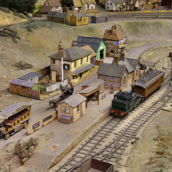 Loco No. 6 and carriage is at Gammon End Station where a hansom cab and a charabanc are waiting.